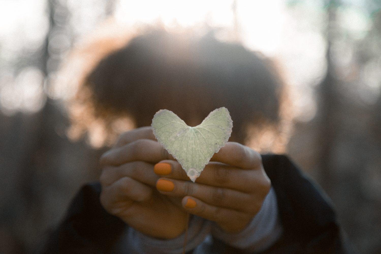 En tjej håller fram ett löv som ser ut som ett hjärta